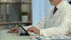 Doctor viewing patients x-rays on tablet in hospital, modern technologies Arkistovideo