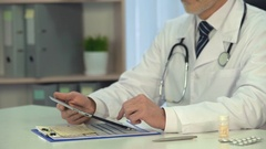 Male physician scrolling information on tablet, on-line consultation, healthcare Stock Footage