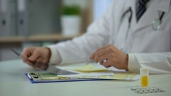 Therapist analyzing patient's lungs x-ray and writing down diagnosis, treatment Stock Footage