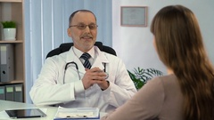 Recovered female patient talking to satisfied physician in clinic, health care Stock Footage