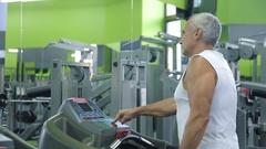 Old man runs on a treadmill Stock Footage