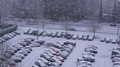 Aerial view of traffic flow and parking lot on cold blizzard snow winter day Stock Footage