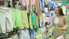 Woman take to cart clothes for newborn in store Stock Footage
