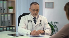 Experienced doctor listening to patient and filling out registration form Stock Footage