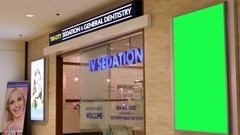 Green billboard for your ad on wall beside dentistry store Stock Footage