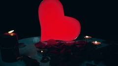 Glowing heart with flames candles rotate on valentine table theme, slow motion Stock Footage