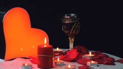 Glowing heart with flames candles and rose petals, gothic cupe rotation Stock Footage