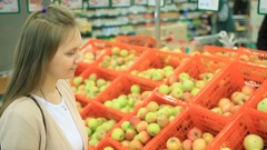 Young woman buy fruit apples at market Stock Footage