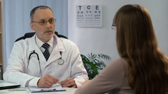 Eye examination, ophthalmologist choosing eyeglasses for patient, checkup Stock Footage