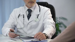 Doctor typing patient's data on tablet, keeping medical records, consultation Stock Footage