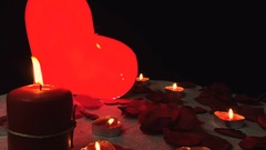 Glowing heart with flames candles and rose petals, valentines day, slow motion Stock Footage