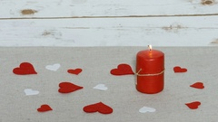 Young woman arranges table with red and white hearts and put a flame red candle Stock Footage