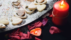 Heart cookies, rose petals and flamed candles. turning the table motion Stock Footage