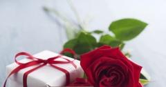 Three red roses with gift box and paper card with i love you phrase on blue wood Stock Footage