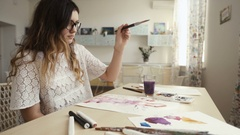 Female artist paints a picture. Drawing in art studio. Stock Footage