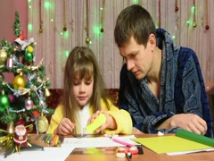 Dad is watching a daughter element sticks to the New Year's hand-made article Stock Footage