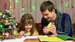 Dad helps daughter glued to the element of a Christmas hand-made article Stock Footage