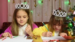 Sisters swearing and jostling drawing at a table in a Christmas setting Stock Footage