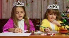 Two girls in dressing gowns sitting at a table and writing a letter to Stock Footage