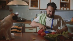 A man cooks in the kitchen beside him sits a funny beautiful cat Stock Footage