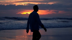Silhouette of man walking ont the beach during sunset, super slow motion Stock Footage
