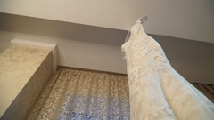 View of the unusual wedding dress hanging in the room, slidecam Stock Footage