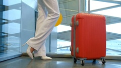 Shooting from down blonde woman standing, waving hand in airport Stock Footage