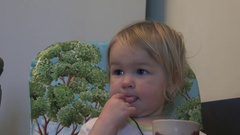Little girl in the dining room at the table and licked his hand touches herself Stock Footage