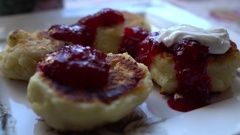 Close-up cheese pancakes with berry jam and sour cream. Slow Motion. HD Stock Footage