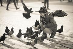 Girl age 6-8 years feeding pigeons at main square in old city Stock Photos