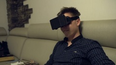 Young cheerful Man Wearing VR Headset at Living Room. Using Gestures with Hands Stock Footage