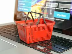 Online shopping e-commerce concept. Shopping basket on laptop keyboard. Piirros