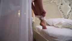 Happy beautiful bride slowly wears a garter on leg Stock Footage