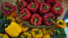 Harvest ripe tasty red, green and yellow bell peppers on a shop window Stock Footage