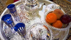 Silver Arabic tea set with a vase of fruit on a Persian rug Stock Footage