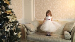 Little girl standing awkwardly on the couch and playing with dress Stock Footage