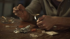 Young male withdrawing heroin dose with syringe from spoon, man abusing drugs Stock Footage