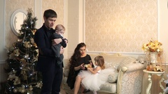 Beautiful family in an ornate building near the Christmas tree Stock Footage
