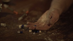 Man losing consciousness or dying of drug overdose, handful of pills on table Stock Footage