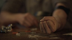 Hand of depressed man making drug injection with syringe at abandoned place Stock Footage