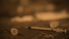 Table covered with used syringes and drug powder, addicted person needs help Stock Footage