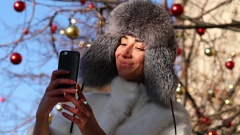 Salfie. Young woman in gray fur head cloth outdoor in winter Stock Footage