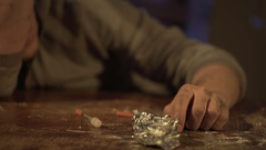 High drug addict losing consciousness after injection, syringe in hand on table Stock Footage