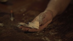 Unconscious drug addict, hand full of pills and cocaine powder falling on table Stock Footage