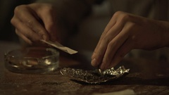 Young man's hands rolling cigarette of medical marijuana to relieve chronic pain Stock Footage