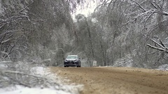 Tree branches bent under the weight of snow and ice over the road Stock Footage