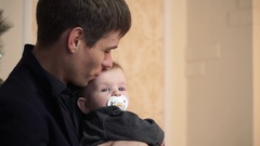 Serious father tenderly kisses the small son Stock Footage