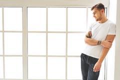 Young man dreaming near window Stock Photos