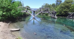 Drone scene of old wooden bridge over blue transparent patagonia river Stock Footage