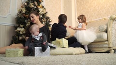 Little beautiful family with gifts under the Christmas tree Stock Footage